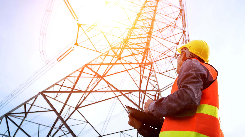 Eine Person steht vor einem Strommast.