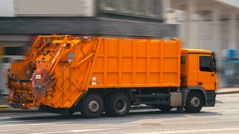 Orangener Müllabfuhrwagen.