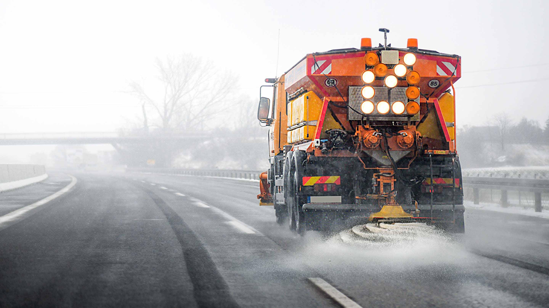 Ein Winterdienstwagen fährt eine Straße entlang und streut Salz.