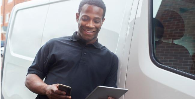 Hombre apoyado en una furgoneta blanca con dos dispositivos en sus manos