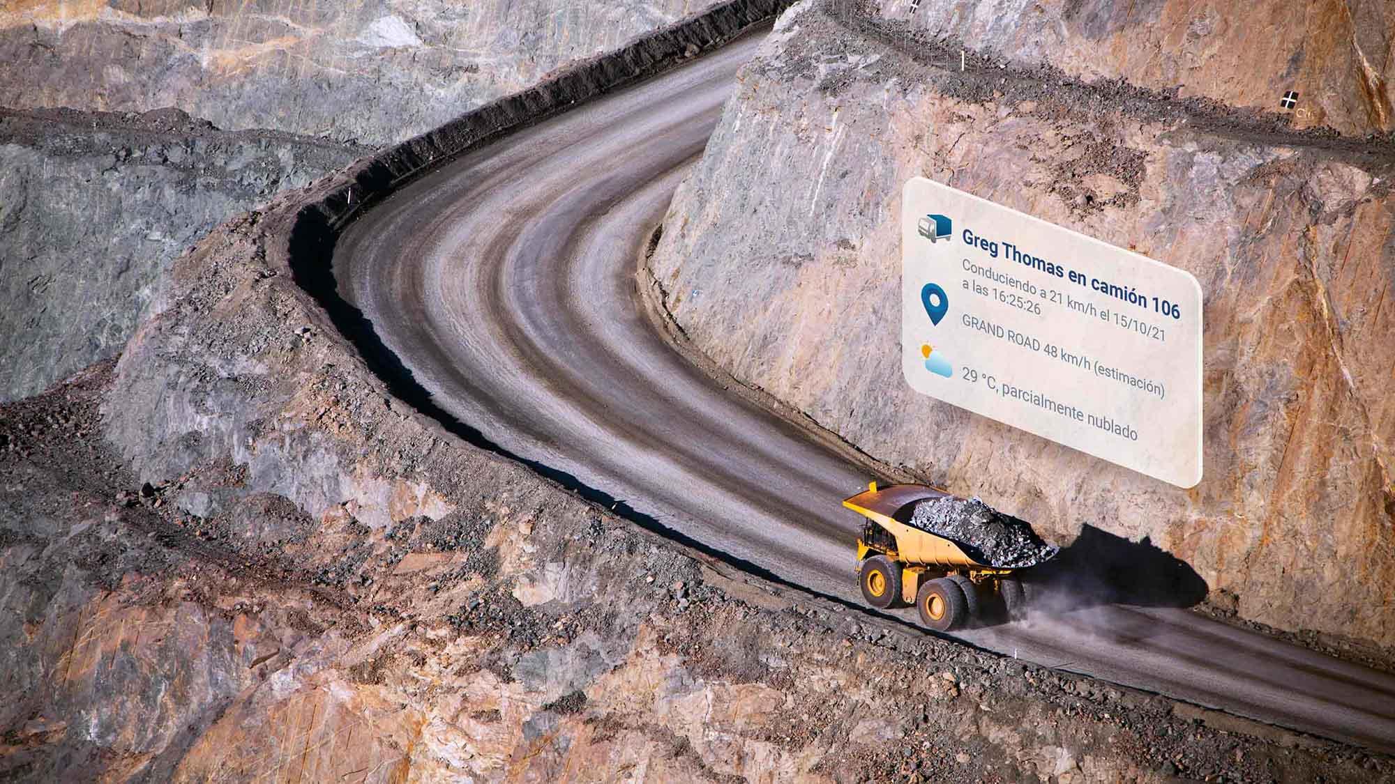 Camión volquete amarillo conduciendo por un camino de tierra curvo con elementos de interfaz de usuario MyGeotab encima
