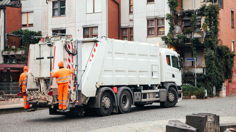 Camión de basura levantando un contenedor azul