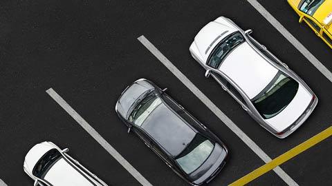 La imagen muestra varios vehículos aparcados en batería desde un plano picado