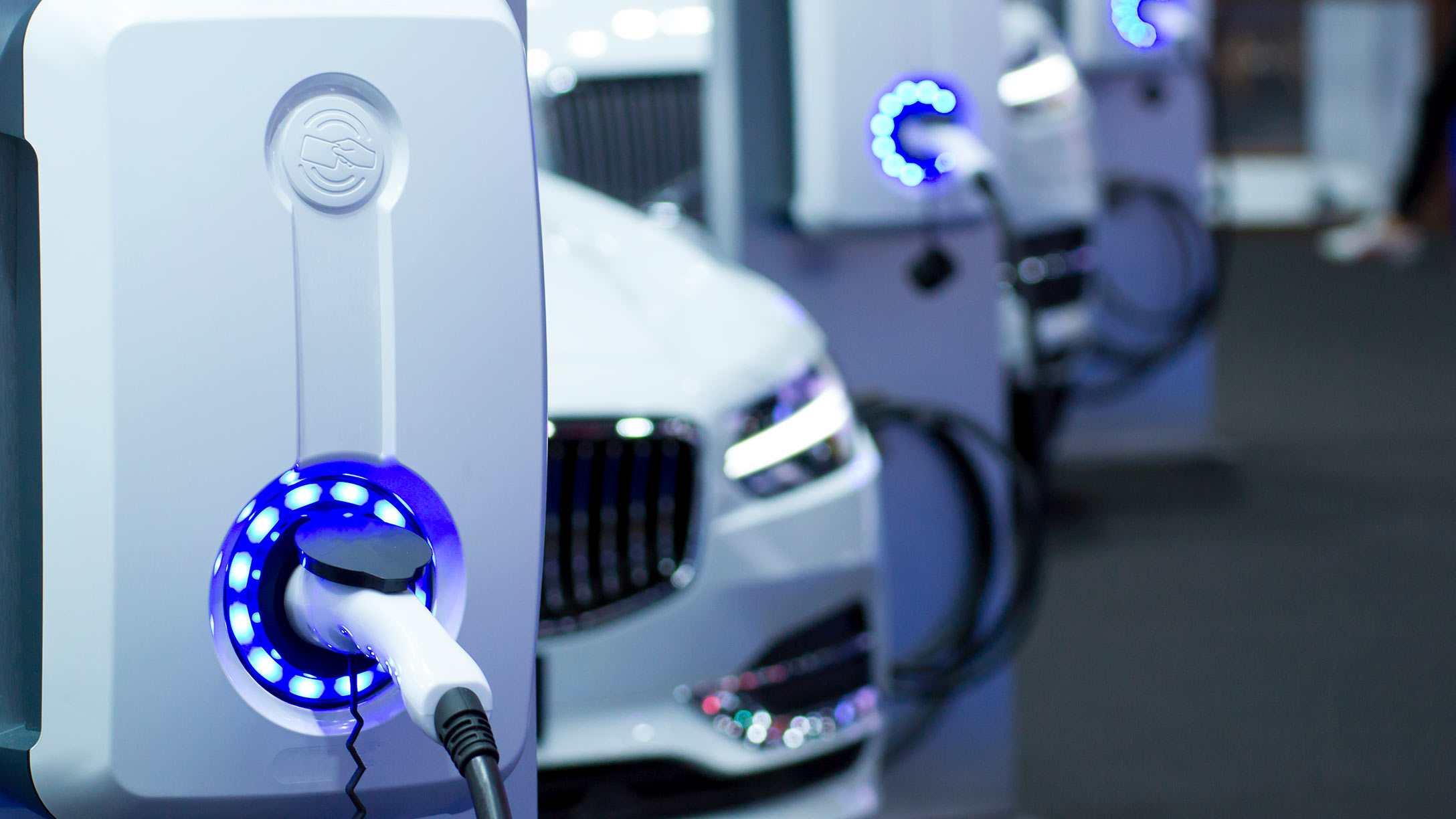 Imagen de una fila de vehículos eléctricos blancos cargando