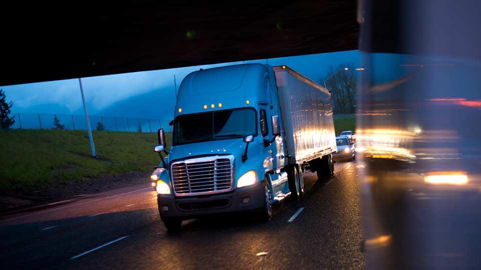 Camión blanco conduciendo en la noche en una carretera con otros vehículos alrededor