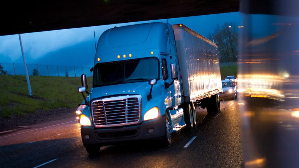 Truck passing under bridge at dusk