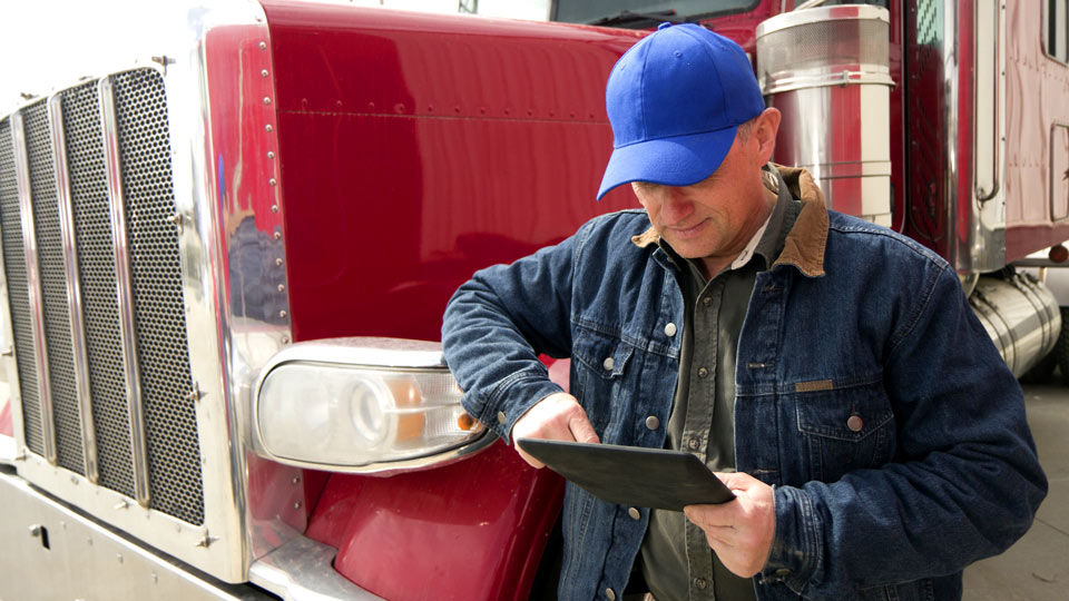 Man using tablet leaning up against red truck
