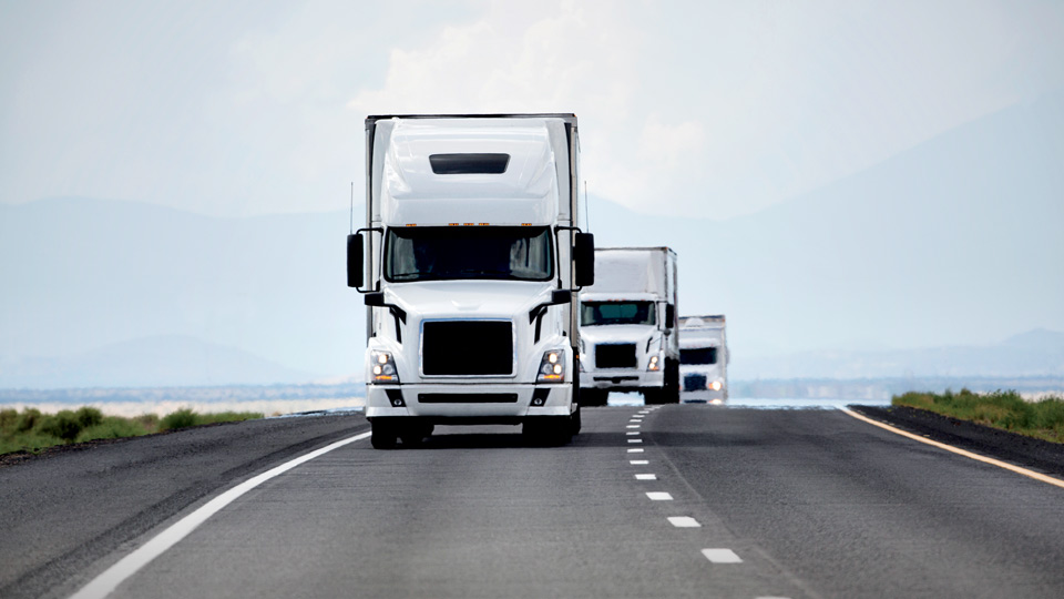 A line of white trucks driving down a road