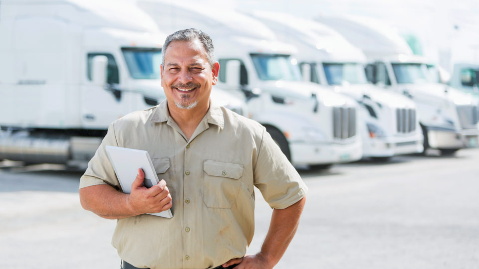 A man in a tan shirt standing in front of lineup of white trucks