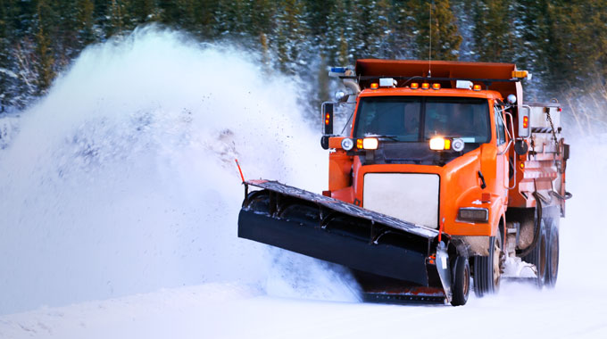 Orange snow plow plowing snow