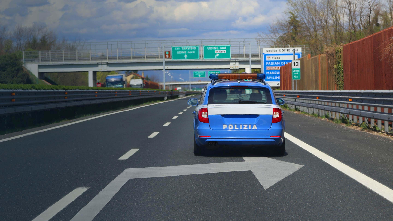 Auto della polizia che guida lungo una strada