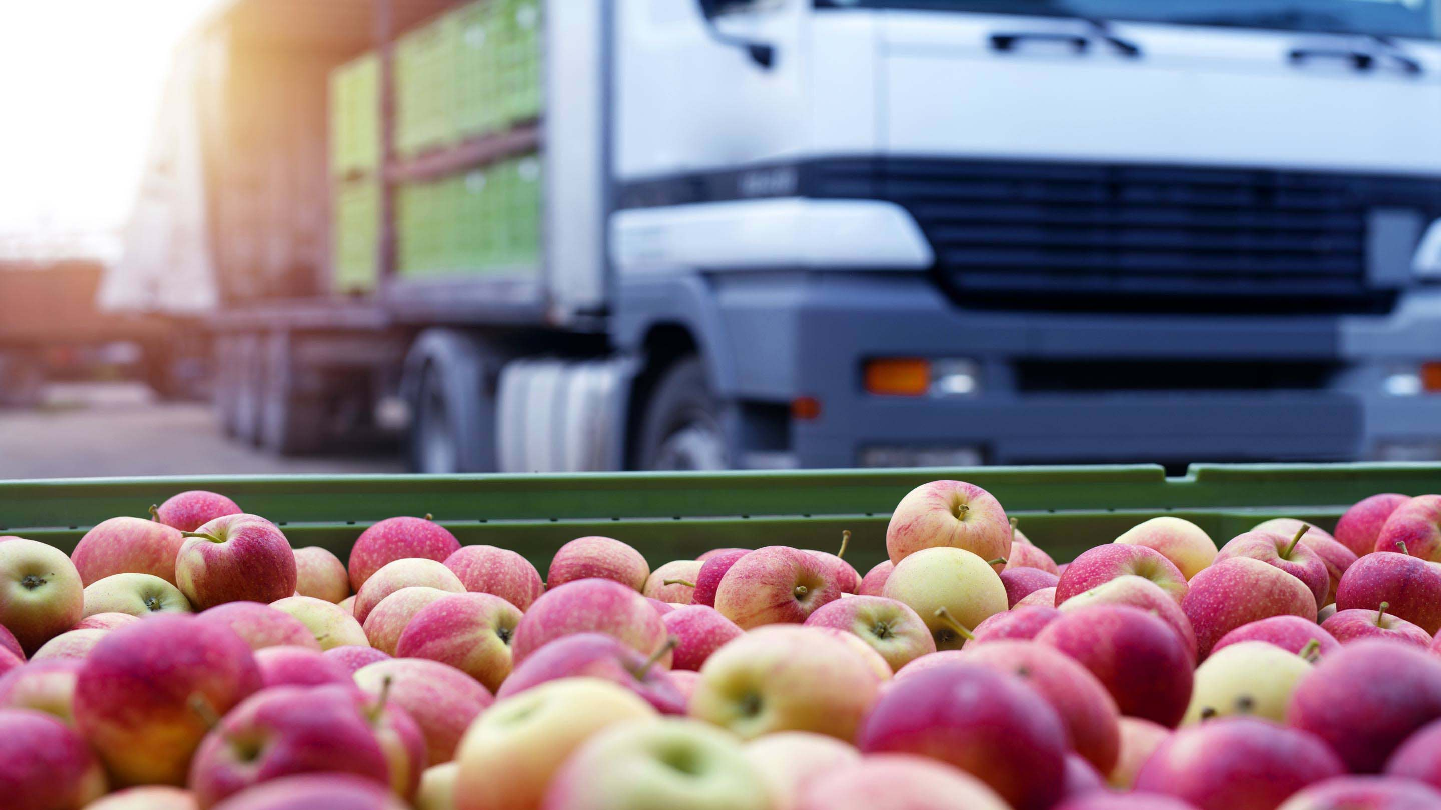 A tray of apples in the foreground with a white food delivery truck in the background