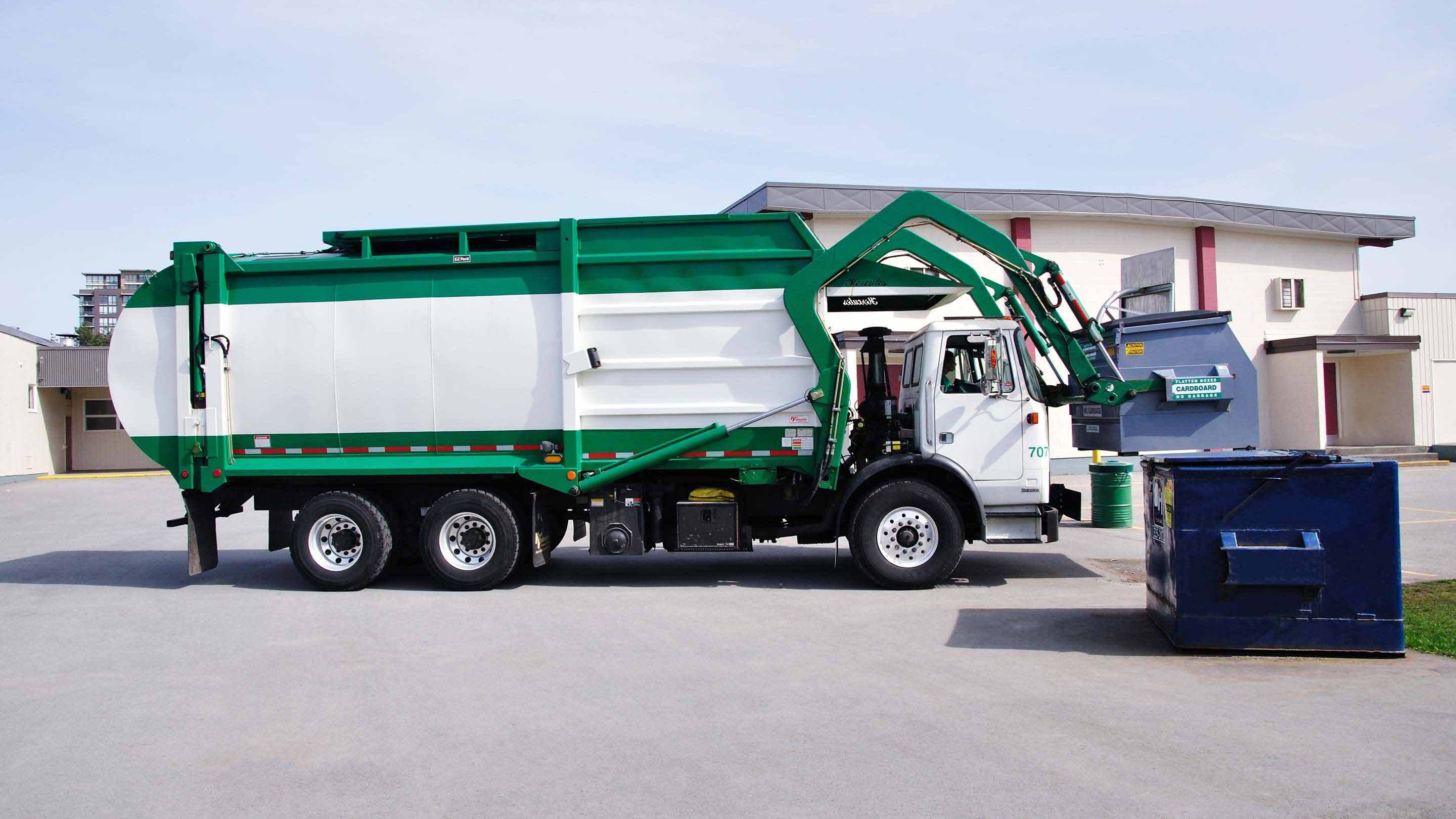 Green and white garbage truck lifting a blue dumpster