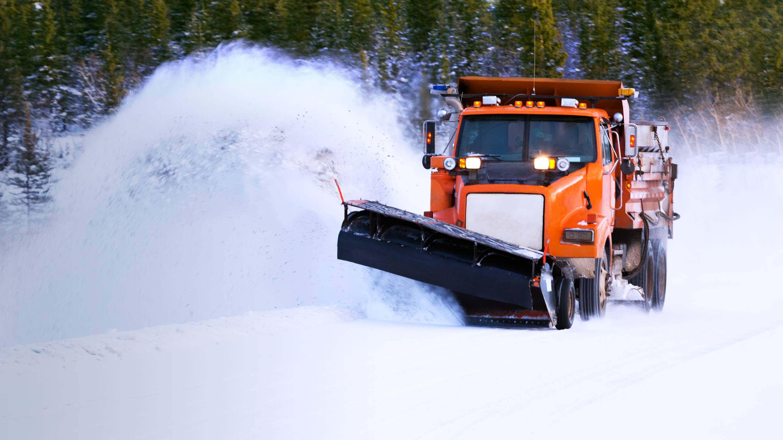 Un camion orange roulant en hiver