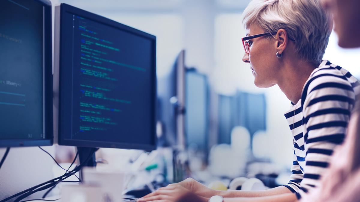 Una mujer escribiendo código, sentada frente a un monitor de ordenador.