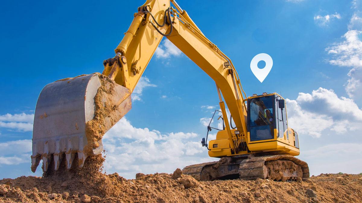 Vehículo de construcción amarillo grande cavando en la tierra con un símbolo de GPS blanco encima