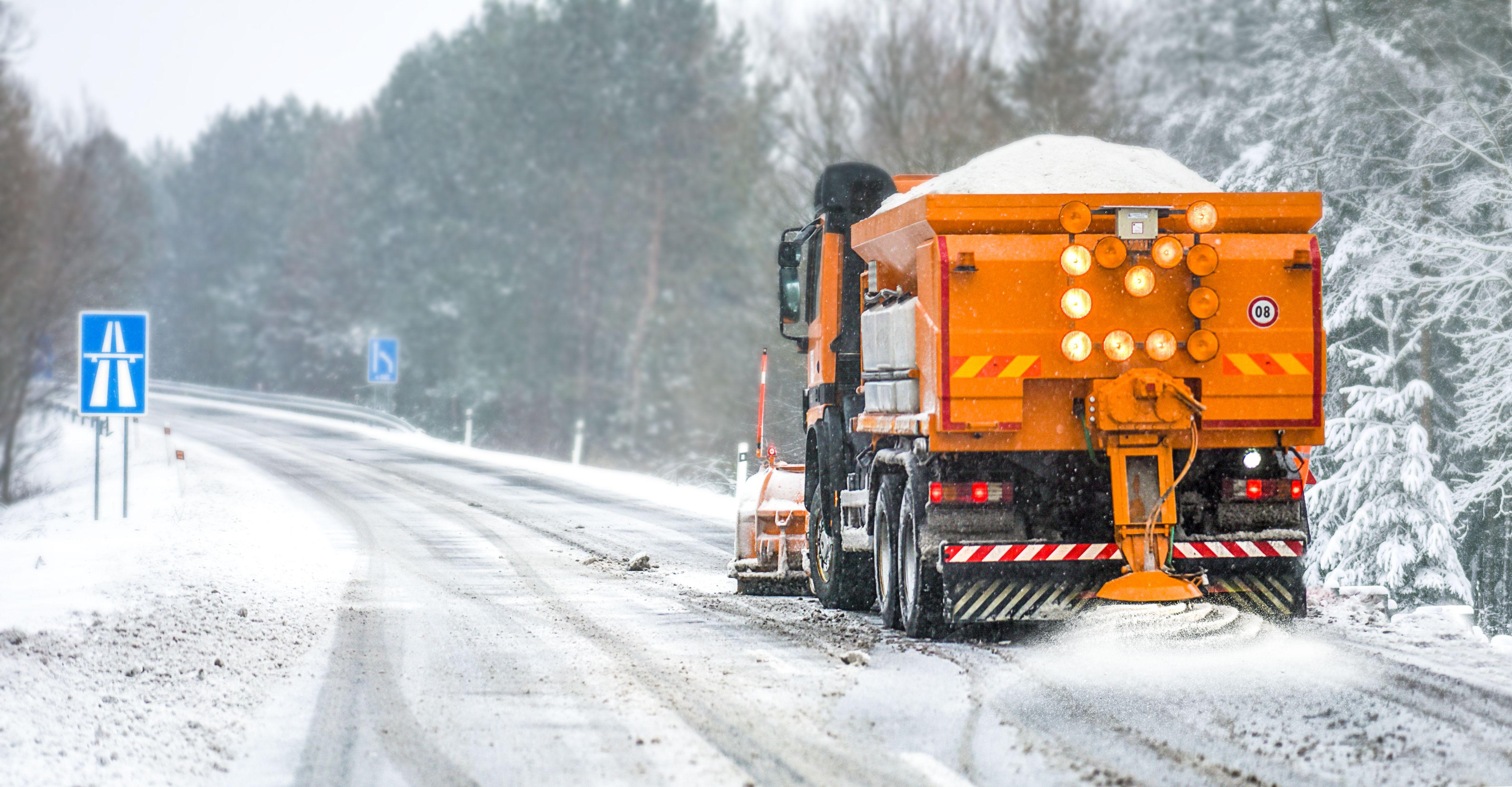 Orange snow plow driving down an empty road