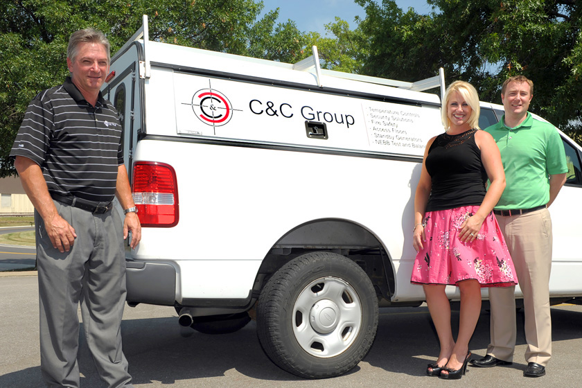 Three people standing in front of a C&C branded pickup truck