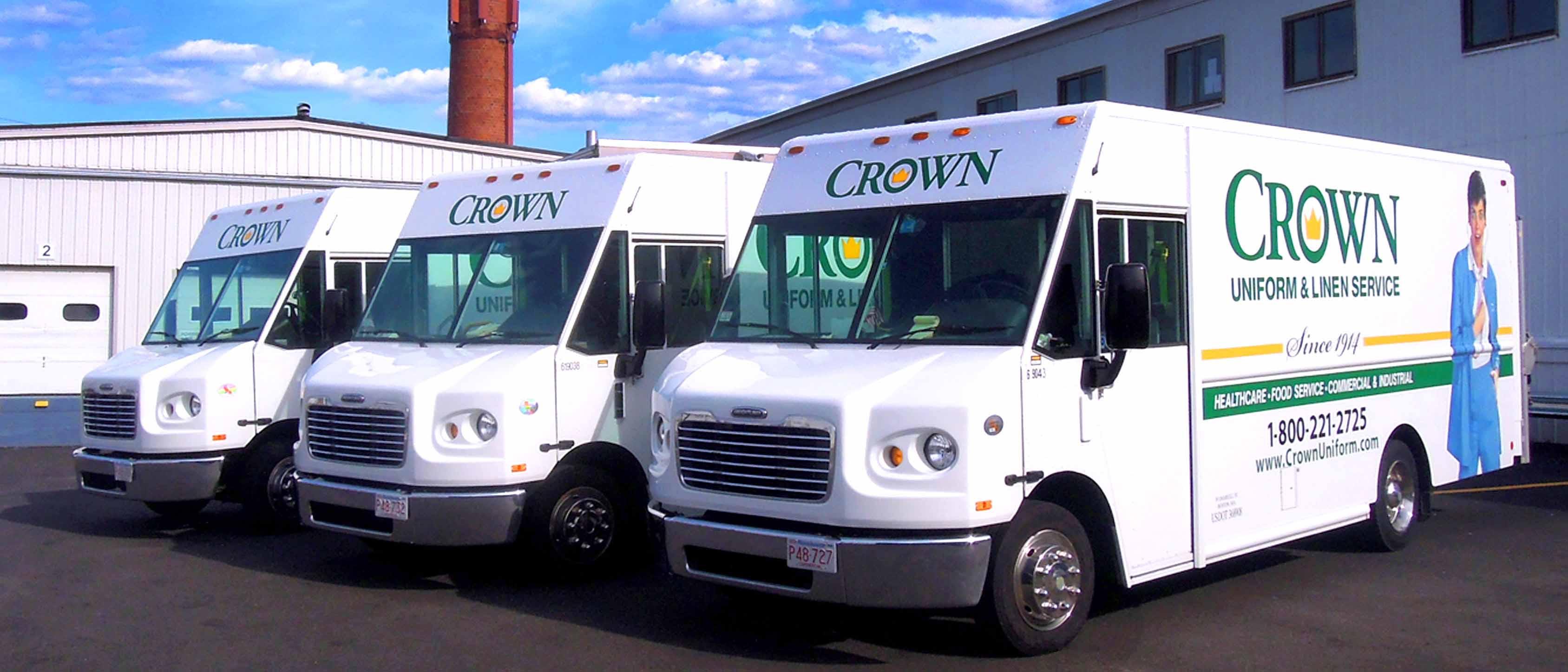 Three parked CROWN Uniform & Linen Service trucks