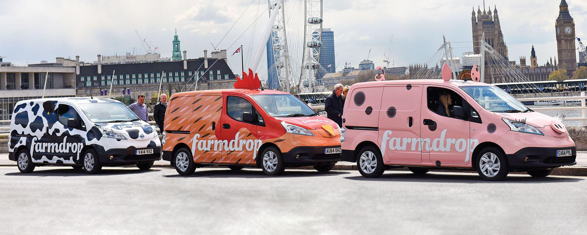Trois fourgons Farmdrop multicolores roulant sur une route de Londres