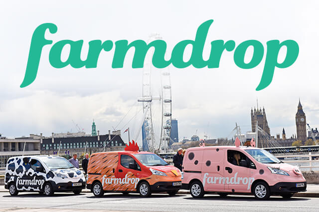 Three delivery vans lined up with London in the background. One vehicle is painted like a cow, one is painted like a chicken and one is painted like a pig.