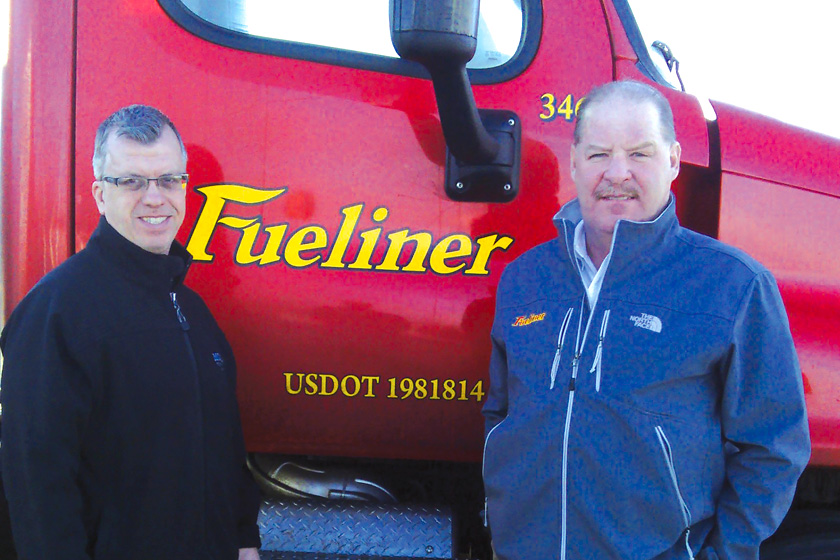 Two men standing in front of a red Fueliner truck