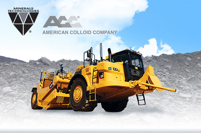 Yellow mining equipment with surface pit in background and company logo in left hand corner.