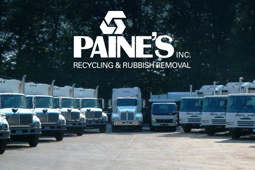 A lineup of white waste and recycling vehicles