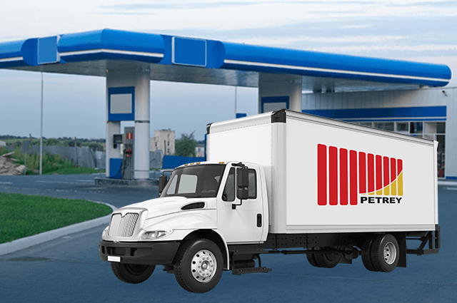White delivery box truck with company logo on it and blue gas station in the background.