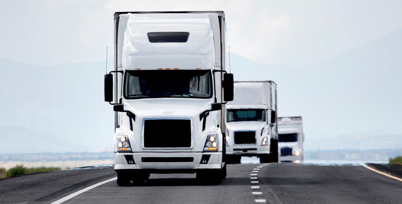 Three white trucks platooning down an open road