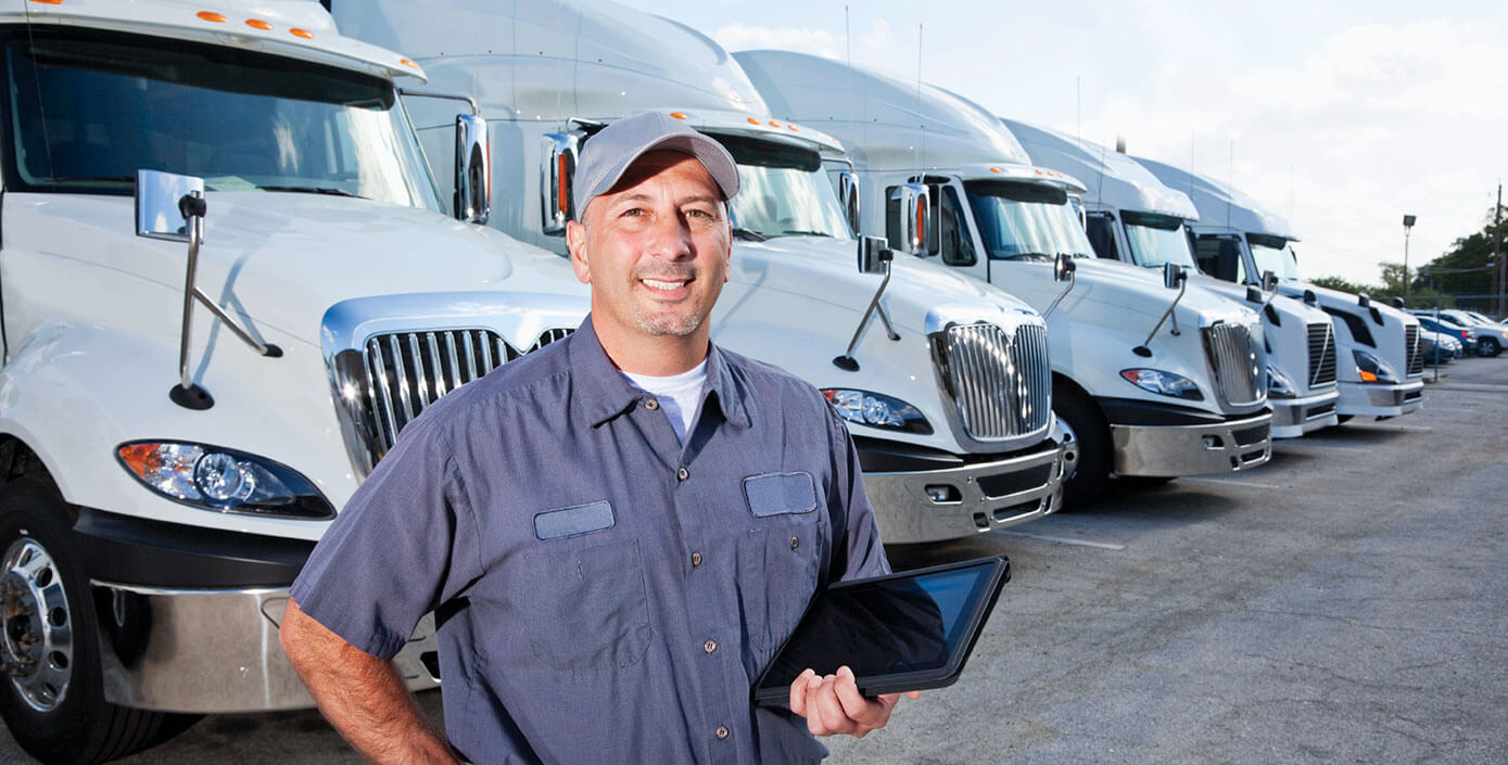 Fleet manager smiling in front of four transportation vehicles