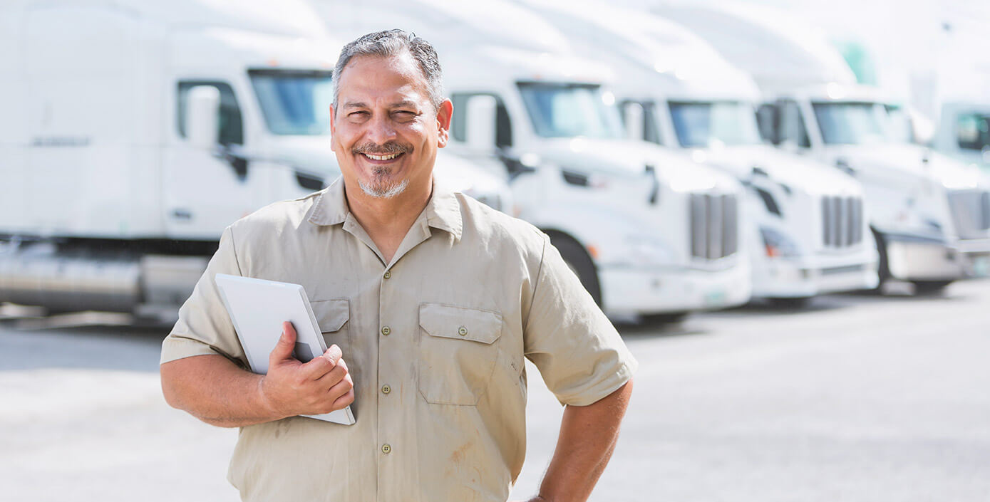 Truck manager smiling in front of transportation trucks