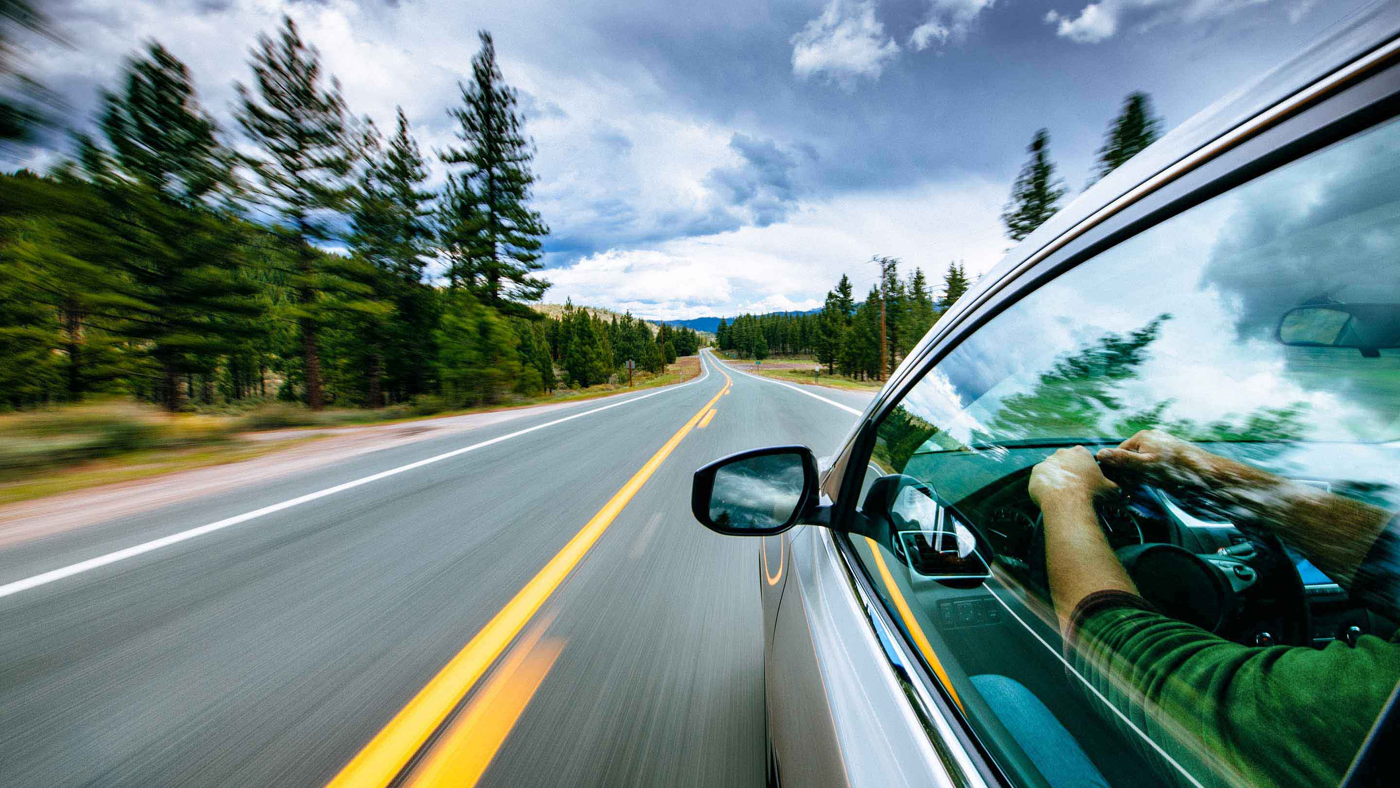 Photo of a person driving down the road in a silver car