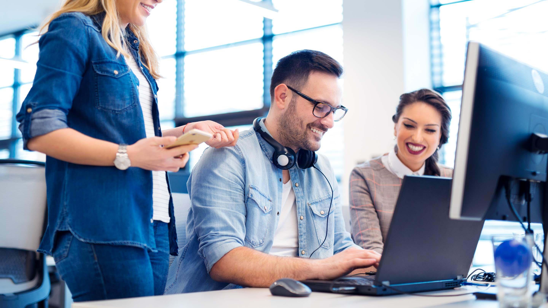 男人和女人微笑着在他们的电脑上提供在线支持