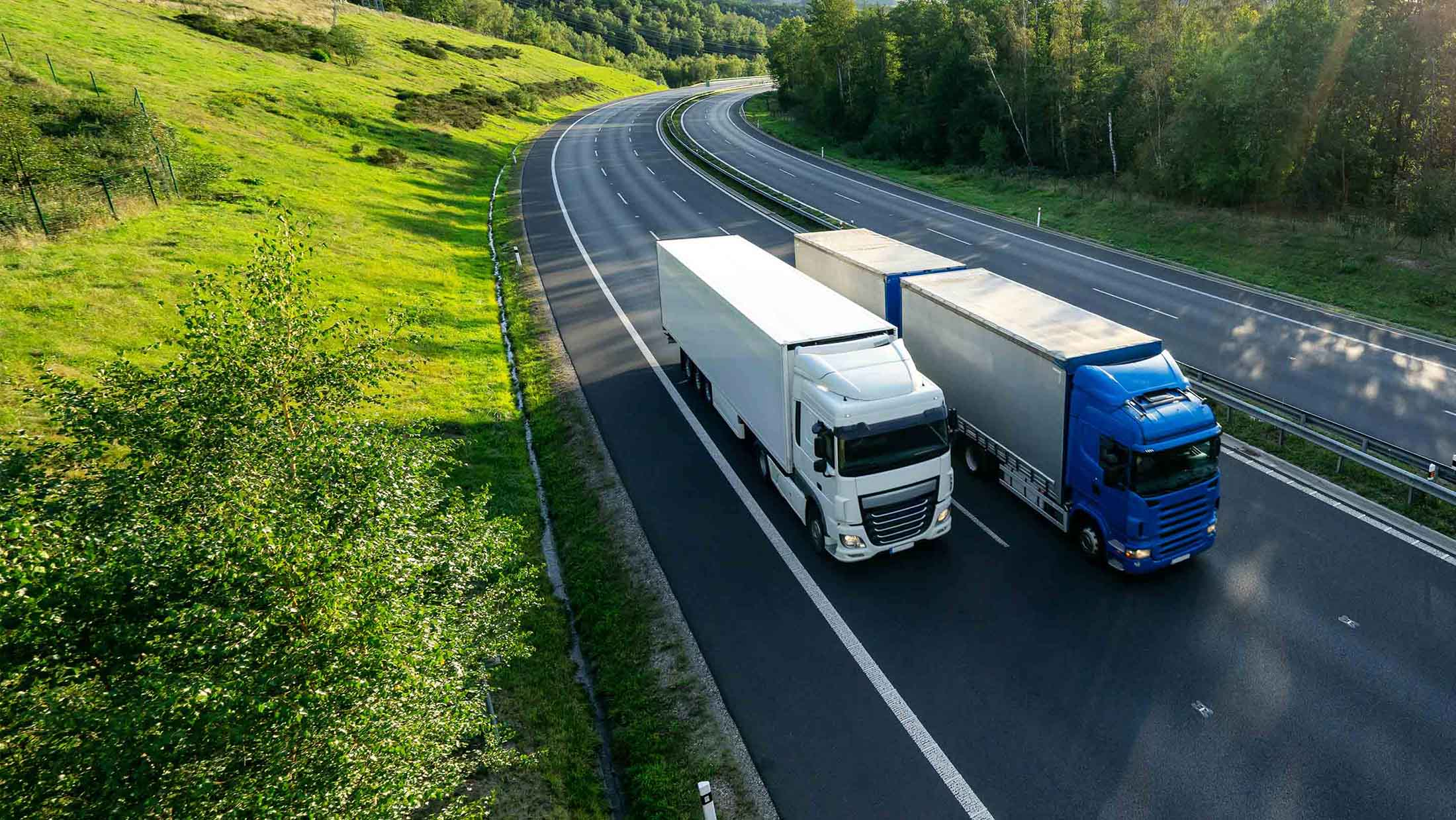 Two trucks with tachographs installed, driving side by side.