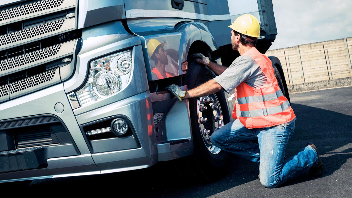 Man kneeling next to a truck checking its tire