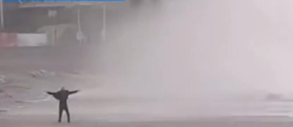 老人在颱風天站海浪中拍照險些遭沖走。(圖/翻攝自「都市時報」微博)