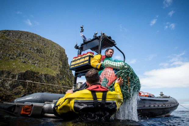 Crew from the Beluga II load plastic cleaned from beaches on Eilean Taighe into a rhib to be taken and disposed of.