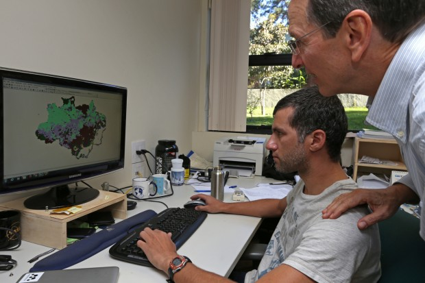 Greenpeace campaigners studying map on a screen