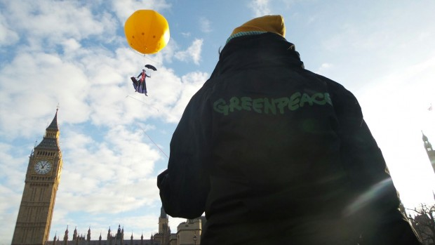 Greenpeace activist watches giant yellow balloon with Mary Poppins fly over the Palace of Westminster