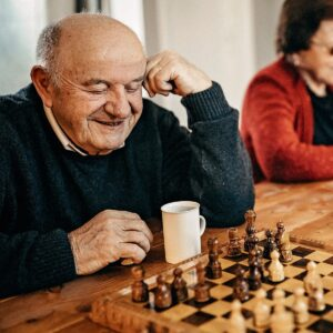 Elderly man playing chess while drinking a coffee