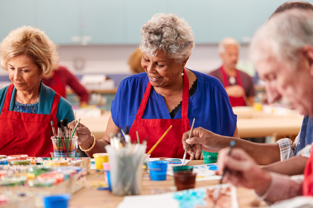 Seniors painting together in a class