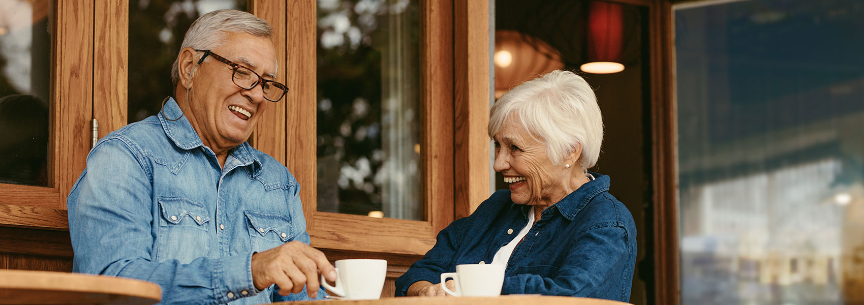 An elderly couple chatting and laughing while drinking coffee