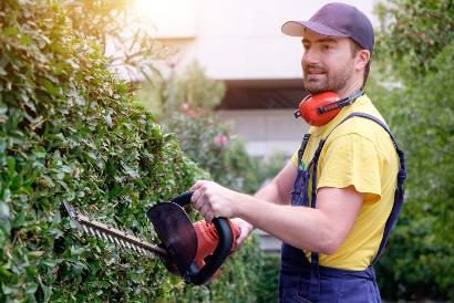 man trimming bushes in a senior living facility