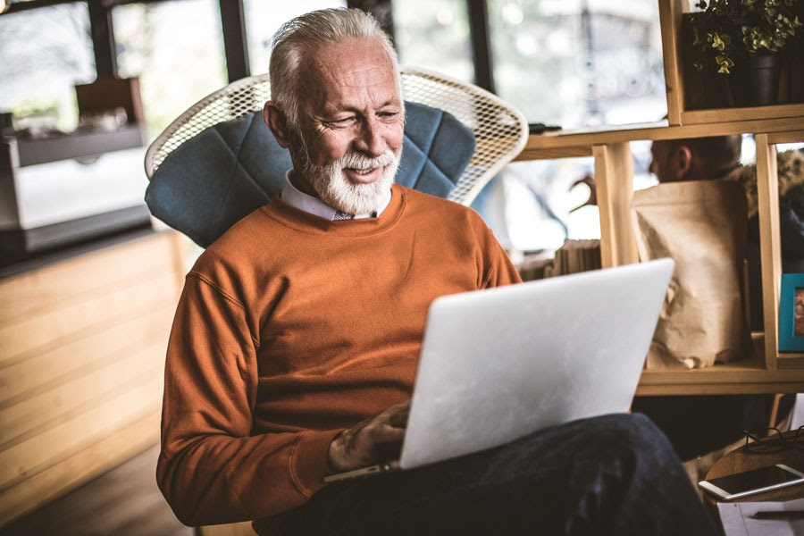 Senior man looking at his laptop while sitting in a chair