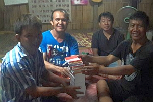 Pastor Surachay, with Boy and Lot, handing over GRN materials to a Black Lahu villager
