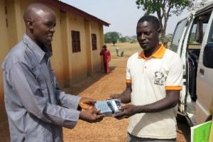 One of the GRN team handing a Saber mp3 player to a villager