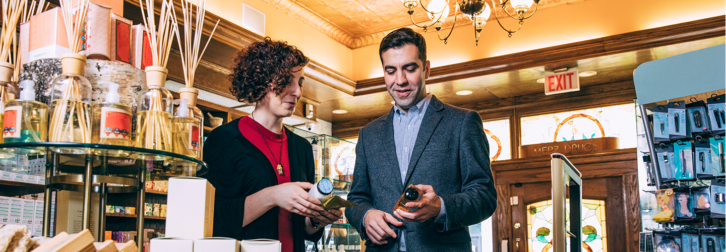 Anthony Qaiyum, President of Merz Apothocary in Chicago, IL helping a customer find a product