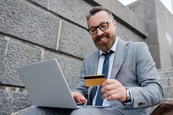 A man smiling in front of his laptop holding a credit card