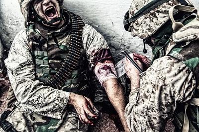 Military medic binding gunshot wound during fight
